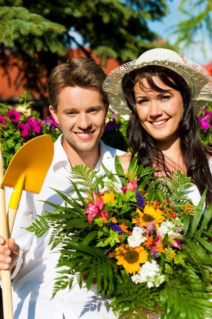 Glückliches paar mit dem blumenblumenstrauß und gartenarbeitwerkzeugen, die im garten aufwerfen Premium Fotos