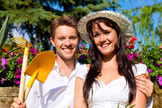 Glückliches paar mit gartengeräten im sonnenbeschienen blumengarten Premium Fotos