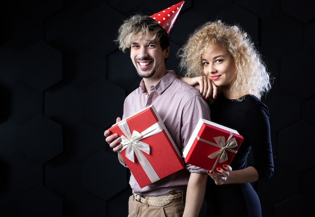 Glückliches paar mit geschenkboxen, kamera mit lächeln betrachtend. feier und romantisches konzept. Premium Fotos