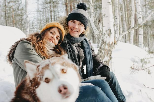Glückliches paar mit hund haski am waldnaturpark in der kalten jahreszeit. Premium Fotos