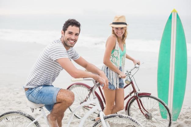 Glückliches paar mit ihrem fahrrad am strand Premium Fotos