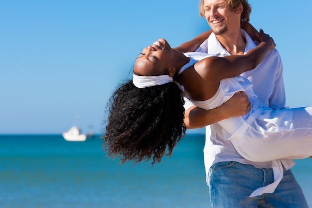 Glückliches paar - schwarze frau und kaukasischer mann - am strand in ihren ferien Premium Fotos