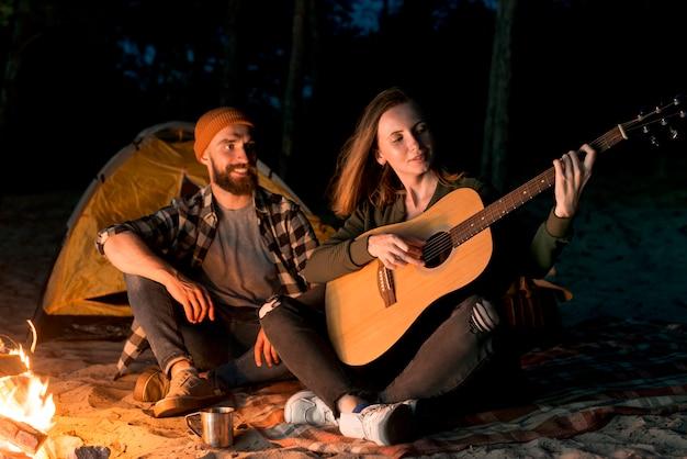 Glückliches paar singen und gitarre spielen Kostenlose Fotos