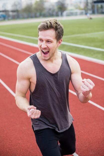 Glückliches porträt des aufgeregten jungen mannes, der seine faust im stadion zusammenpreßt Kostenlose Fotos