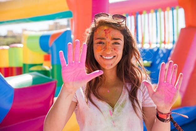 Glückliches porträt einer jungen frau, die holi farbhände zeigt Kostenlose Fotos