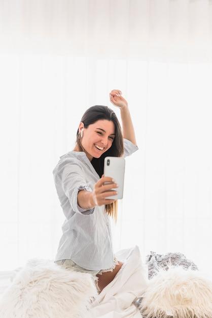 Glückliches porträt einer jungen frau, die selfie auf smartphone nimmt Kostenlose Fotos