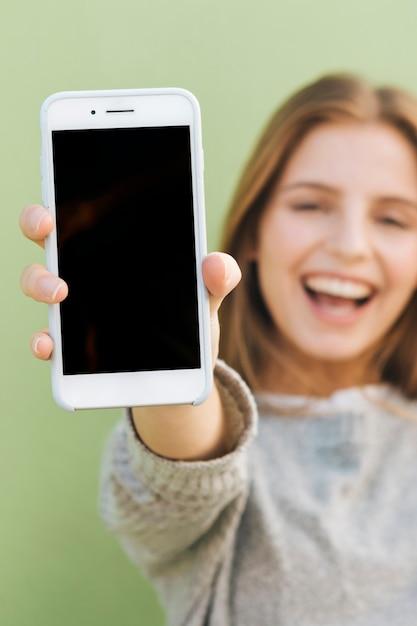 Glückliches porträt einer schönen jungen frau, die smartphone in richtung zur kamera hält Kostenlose Fotos