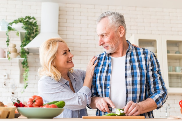 Glückliches porträt von den älteren paaren, die das lebensmittel in der küche zubereiten Kostenlose Fotos