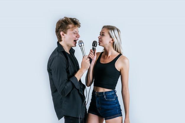 Glückliches porträt von den paaren, die mikrofon halten und singen ein lied Kostenlose Fotos