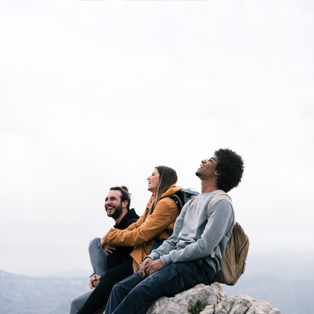 Glückliches porträt von junge freunde, die auf bergspitze sitzen Kostenlose Fotos