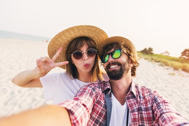 Glückliches reisendes paar in der liebe, die ein selfie am telefon am strand nimmt Kostenlose Fotos