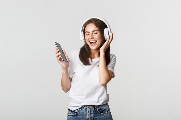 Glückliches schönes brünettes mädchen tanzt und hört musik in kabellosen kopfhörern, hält smartphone. Kostenlose Fotos