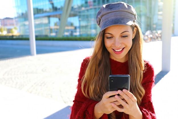 Glückliches schönes mädchen, das smartphone in der modernen stadt verwendet. mode herbst winter mädchen porträt. Premium Fotos