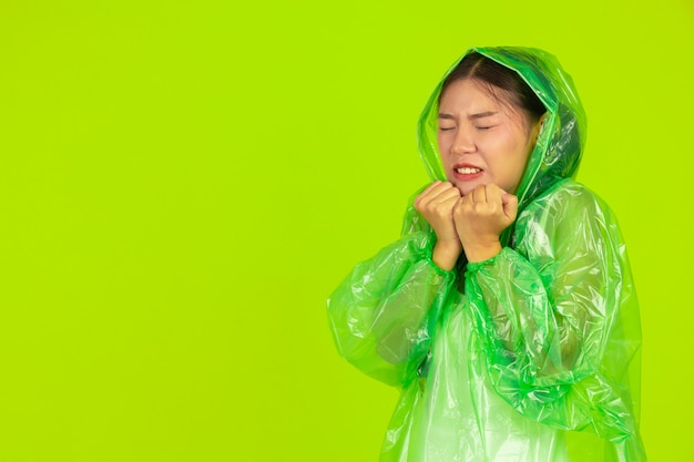 Glückliches schönes mädchen, grüne kleidung, regenschirm und mantel, regnerischer tag tragend. Kostenlose Fotos