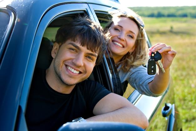 Glückliches schönes paar, das die schlüssel zeigt, die im neuen auto sitzen Kostenlose Fotos