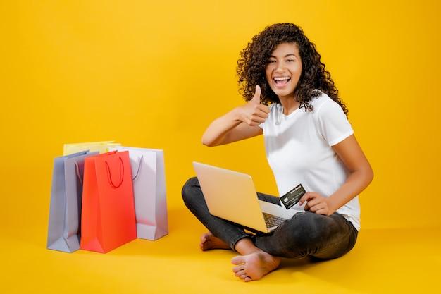 Glückliches schwarzes mädchen mit den bunten einkaufstaschen, die mit dem laptop und kreditkarte lokalisiert über gelb sitzen Premium Fotos