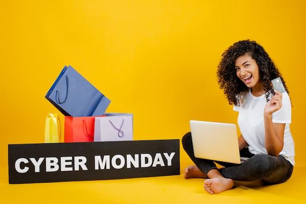 Glückliches schwarzes mädchen mit den bunten einkaufstaschen und cyber montag unterzeichnen das sitzen mit dem laptop und kreditkarte, die über gelb lokalisiert werden Premium Fotos