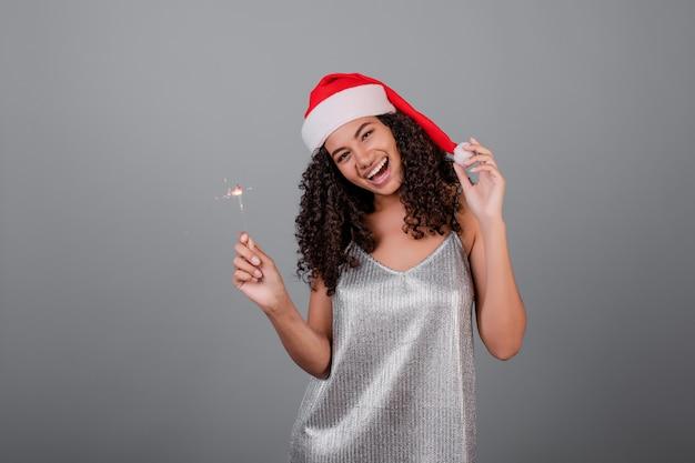 Glückliches schwarzes mädchen mit den funkelnden wunderkerzen, die den weihnachtshut und -kleid lokalisiert über grau tragen Premium Fotos
