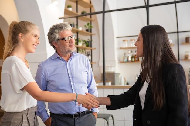 Glückliches, selbstbewusstes weibliches manager-treffen mit kunden und händeschütteln Kostenlose Fotos