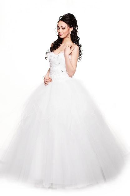 Glückliches sexy schönes brautbrünettmädchen im weißen hochzeitskleid mit frisur und hellem make-up auf weißem hintergrund Kostenlose Fotos