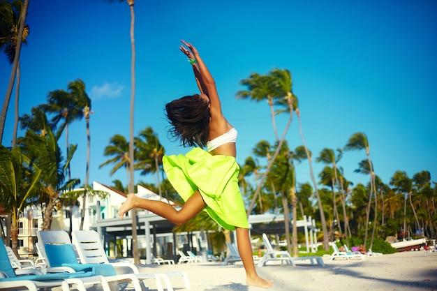 Glückliches städtisches modernes junges stilvolles frauenfrauenmodell im hellen modernen stoff im grünen bunten rock draußen im sommerstrand, der hinter blauen himmel springt Kostenlose Fotos