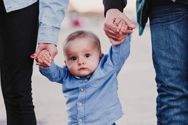 Glückliches stilvolles elternhändchenhalten mit baby und gehen durch die straße, zarter familienmoment. Premium Fotos