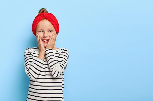 Glückliches stilvolles kleines mädchen mit dem roten stirnband, das aufwirft Kostenlose Fotos