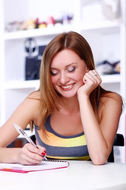 Glückliches studentenmädchenschreiben irgendwie Kostenlose Fotos