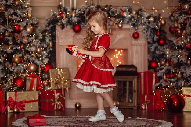 Glückliches süßes kleines blondes mädchen mit langen haaren in einem roten kleid, das auf weihnachten wartet Premium Fotos