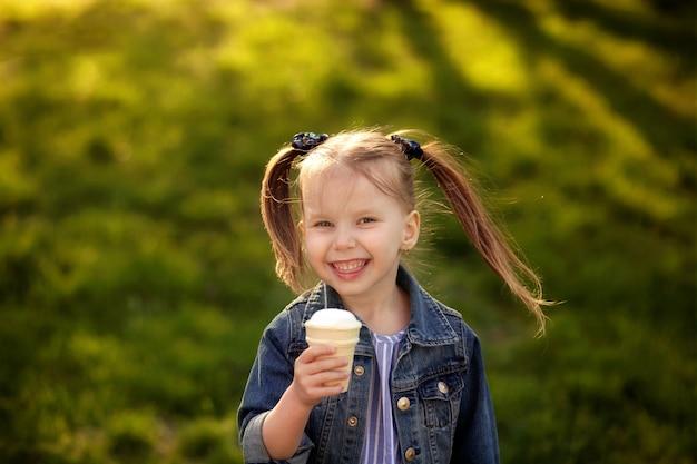 Glückliches süßes mädchen isst eis in der natur an einem warmen sommerabend Premium Fotos