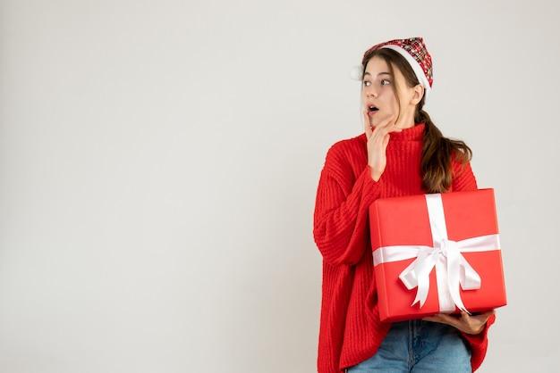 Glückliches süßes mädchen mit weihnachtsmütze, die geschenk hält hand auf ihr kinn stehend auf weiß Kostenlose Fotos