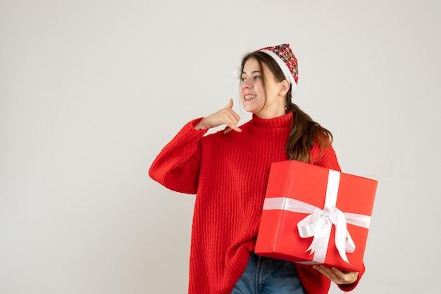 Glückliches süßes mädchen mit weihnachtsmütze, die schweres geschenk hält, das mich zeichen nennt, das auf weiß steht Kostenlose Fotos