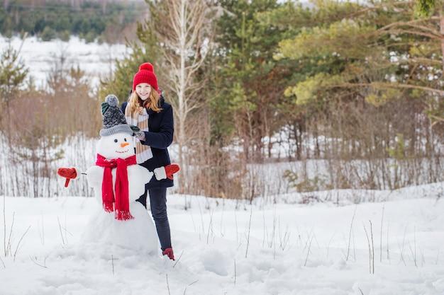 Glückliches teenager-mädchen mit schneemann im winterwald Premium Fotos