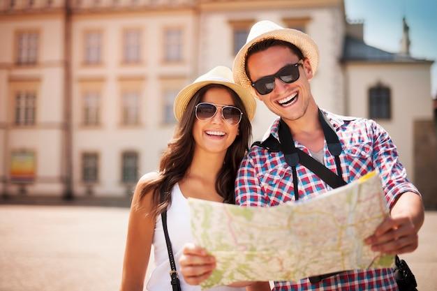 Glückliches touristenpaar, das karte hält Kostenlose Fotos