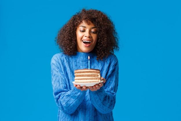 Glückliches verträumtes und hoffnungsvolles geburtstagskind, das wunsch wünscht. attraktive afroamerikanerfrau mit lockigem haarschnitt, luft einatmen, um brennende kerze auf leckerem b-tageskuchen, stehender blauer wand auszublasen. Kostenlose Fotos