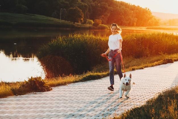 Glückliches weibliches laufen mit weißem hund an der leine während des gehens am parkweg mit wasser und gras mit bäumen auf hintergrundbeleuchtetem hintergrund am abend Premium Fotos