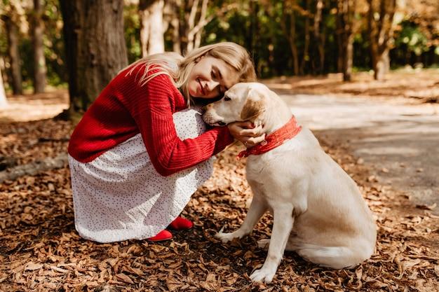 Glückselig glückliches blondes mädchen, das nahe an ihrem hund lächelt. schöne frau, die sich mit geliebtem haustier glücklich fühlt. Kostenlose Fotos