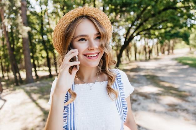 Glückselige junge dame im trendigen strohhut, der während des telefongesprächs lächelt. foto im freien des erstaunlichen weißen mädchens, das freund anruft. Kostenlose Fotos