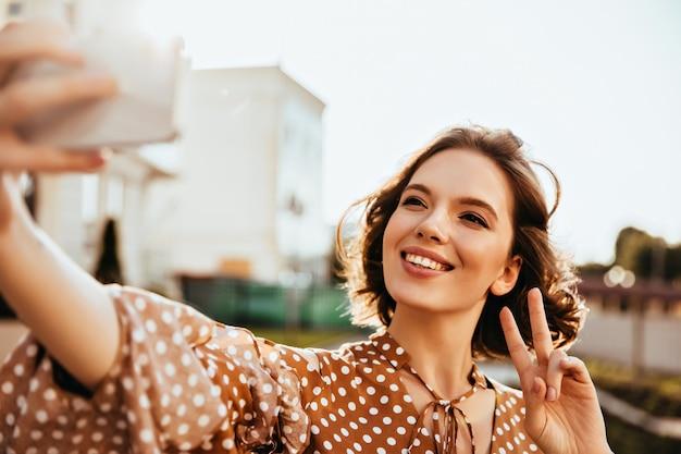Glückselige kurzhaarige frau in braunen kleidern, die glück ausdrücken. jocund dame hält telefon und macht selfie. Kostenlose Fotos