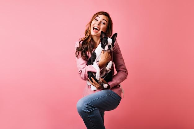 Glückselige rothaarige dame, die niedlichen hund tanzt und hält. innenporträt der romantischen lockigen frau, die positive emotionen während des porträtschießens mit französischer bulldogge ausdrückt. Kostenlose Fotos