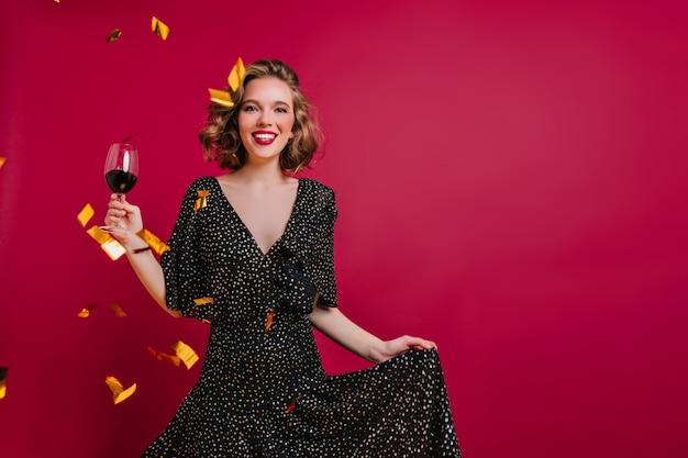 Glückseliges weibliches modell mit glänzendem lockigem haar, das mit weinglas auf bordeauxrotem hintergrund aufwirft Kostenlose Fotos