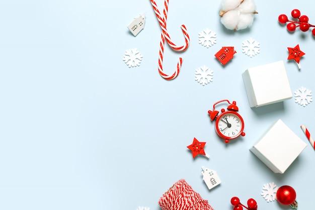 Glückwunschkarte der frohen weihnachten und des neuen jahres mit papierkästen, roter uhr, funkelnunschärfe, autospielzeug, sternen und roter beere auf blauem hintergrund Premium Fotos