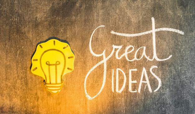 Glühlampe des gelben papierausschnitts mit geschriebenem text auf tafel Kostenlose Fotos