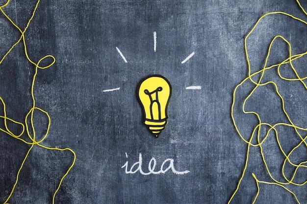 Glühlampe des papierausschnitts mit geschriebenem ideentext und wolle verlegen auf tafel Kostenlose Fotos