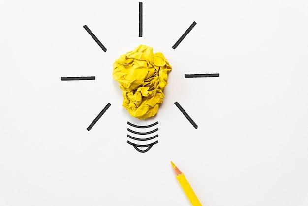 Glühlampe mit zerknittertem buntem papier und gelbem bleistift auf weißem hintergrund. Premium Fotos