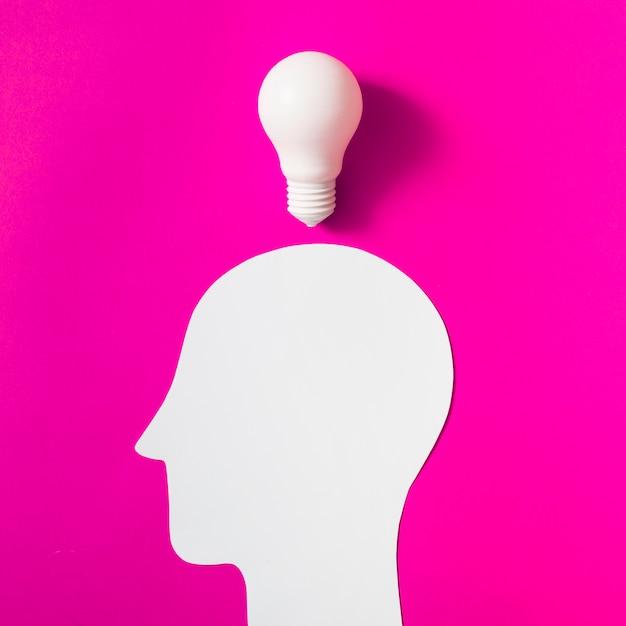 Glühlampe über dem herausgeschnittenen weißen menschlichen kopf auf rosa hintergrund Kostenlose Fotos