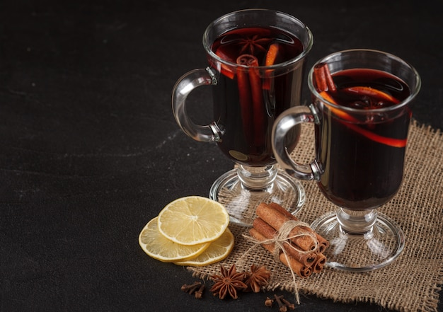 Glühwein-banner. gläser mit heißem rotwein und gewürzen auf dunklem hintergrund. Premium Fotos