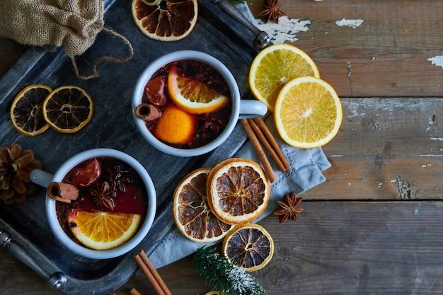 Glühwein in grauen metallbechern mit orange und gewürzen rustikale art Premium Fotos