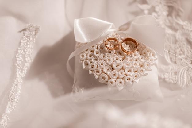 Gold eheringe auf einem spitzenblock. romantisches thema für jungvermählten. hochzeitszubehör Premium Fotos
