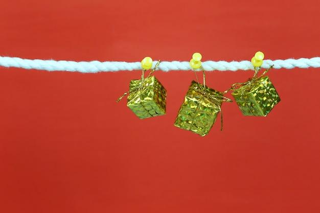 Gold geschenkbox hängen an der wäscheleine. Premium Fotos